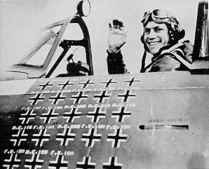 A fighter pilot sitting in an aircraft cockpit, shown in profile, viewed from the left. The pilot is smiling and waving his right hand in the air. The left side of the cockpit bears approximately 25 small black crosses arranged in five rows and five columns.