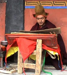 Buddhist monk Geshe Konchog Wangdu in red robe reads Mahayana sutras on stand