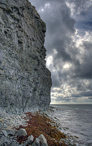 limestone cliffs at the shore with clouds
