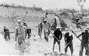 Six men plow the earth in a sinkhole while another walks carrying empty baskets. Three others are standing and walking in the background.