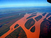 Aerial photograph of a forked river that has turned red due to red soil runoff.