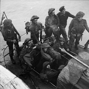 nine British soldiers and one sailor on a small boat at sea. A Union Jack flies from a mast at the rear.