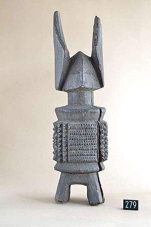 An image of a carved deity named Ikenga, the grey wooden piece has legs, a stylised but simple body, a trinagular head and shallow facial features and two horns around 1/3 its size