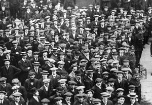 A large throng of people congregate, surrounded by police officers. Approximately half wear peaked caps; the rest wear boaters. Some smile, the rest look pensive.