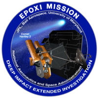 "A circle with a blue border encloses an image of a spacecraft on approach to a comet. The words ""EPOXI Mission"" and ""Deep Impact Extended Investigation"" are written along the border of the image."