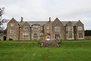 stone building with slate roof, with windows on central two bays, partly obscured by trees