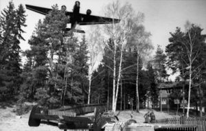 A black-and-white photo of a three-engine aircraft flying over trees. The aircraft is viewed from the front and below. Among the trees is a house with three people standing in front of it. A further aircraft is sitting on the ground and viewed from the rear-right.