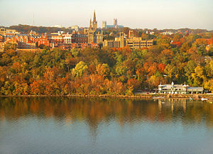 A panorama of numerous buildings, particularly the tall clocktower, above a stretch of brightly colored autumn trees all reflected in a river.