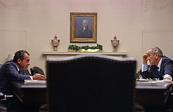 Nixon sits across a large table with Presiden Johnson in the White House