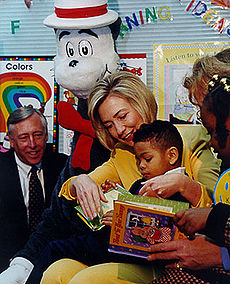 Clinton reads a book to an African-American grade-schooler in Maryland during Read Across America Day in 1998