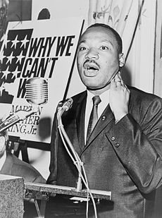 A black and white photograph of Martin Luther King, Jr. speaking at a podium with an enlarged cardboard cover of his book Why We Can't Wait in the background