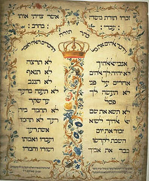 This is an image of a copy of the 1675 Ten Commandments, at the Amsterdam Esnoga synagogue, produced on parchment in 1768 by Jekuthiel Sofer, a prolific Jewish eighteenth century scribe in Amsterdam. It has Hebrew language writing in two columns separated between, and surrounded by, ornate flowery patterns.