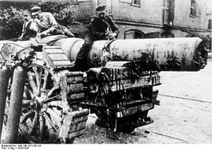 Three men sit on top of a large artillery piece.