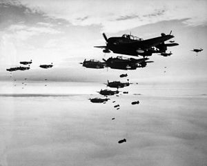 Photograph of a large number of propeller-driven monoplanes dropping bombs