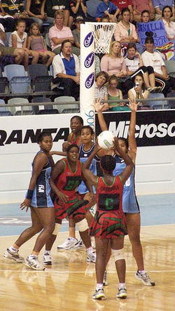 Six players in front of a netball basket. One is in the act of shooting, one is trying to block. Three are in red and three are in blue.