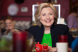 Hillary Clinton dressed in a black suit and a green shirt, sitting in a café. She is smiling, and a red teacup is situated in front of her. The foreground is distorted due to the presence of various small objects.
