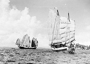 Black and white view of the ocean with an island visible on the horizon to the right. A sailing ship on the left (three sails visible) shows the full length of its hull while another on the right (two sails visible) shows its forward bow.