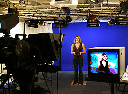 Television studio, with subject in person, with blue screen background, and on television