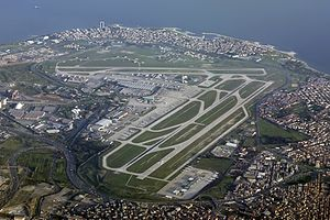An aerial view of an airport with three runways and several taxiways arranged around a terminal