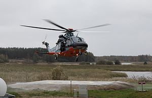 Huey helicopter landing on a pad next to a wetland