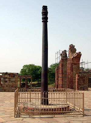 An pillar, slightly fluted, with some ornamentation at its top. It is black, slightly weathered to a dark brown near the base. It is around 7 meters (23 feet) tall. It stands upon a raised circular base of stone, and is surrounded by a short, square fence.