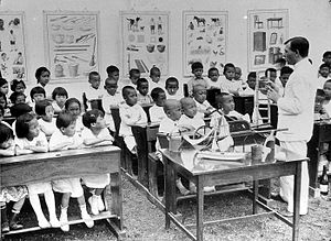 An adult man speaks to several dozen children who are seated on school benches. Behind them on the wall are hanging posters containing various diagrams.