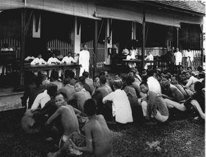 Several dozen men are in squatting positions in front of building. Inside, men dressed in white are sitting behind tables and standing by.