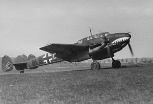 A black-and-white photograph of a twin-engine fighter aircraft standing on a grass field, shown in profile, viewed from the right. The aircraft is appears grey, with a teethed mouth painted on the nose. The twin rudder at the rear bears a black swastika. Further decorations include lines, black and white crosses on the body and on bottom of the wing; a number M8 is visible. The landing gear is extracted and the propellers are turning.