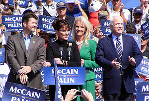 "Todd Palin, Sarah Palin (behind a podium), Cindy McCain, John McCain together on an outdoor stage during daytime, crowd holding blue-and-white ""McCain Palin"" signs around them"