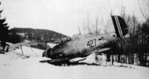A black-and-white photo of a biplane sitting on the ground, shown in semi profile, viewed from the left-rear. The left wing and nose is buried in the ground. The aircraft is marked with the number 427.