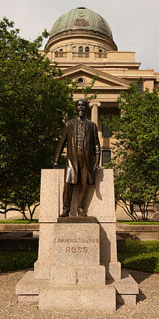 "A large domed building overlooks a full-length statue of balding white male with a mustache and long goatee and wearing a knee-length coat. The pedestal is engraved ""Lawrence Sullivan Ross""."