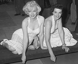 Monroe, wearing a white halterneck dress, is pictured with Jane Russell in a similar dress. They are sitting down on the ground and writing their names on wet cement outside Grauman's Chinese Theatre.