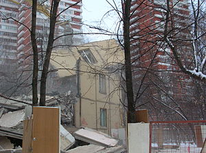 The remains of a low rise building are seen between two high rises