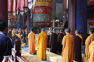 Buddhist monks in saffron robes standing performing a ceremony in Hangzhou, China