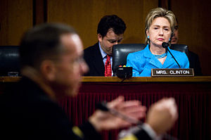 "Clinton listens as the Chief of Naval Operations, Admiral Michael Mullen, responds to a question during his 2007 confirmation hearing with the Senate Armed Services Committee. She is in the background, sitting behind a desk with a placard bearing the words ""MRS CLINTON"", and is wearing a blue suit. A man wearing a black suit sits behind Clinton, taking notes."