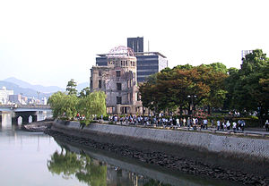 A shot along a river. There is a bridge in the distance, and a ruined domed building in the middle distance. People walk along the footpath that runs parallel to the river.