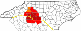 Counties most commonly associated with Metrolina are in dark red, counties often included are light red, and counties sometimes included are in orange. The NC/SC state line is shown in yellow.