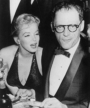 Monroe seated at a dinner table and wearing a low-cut dress while speaking to Arthur Miller in a tuxedo.