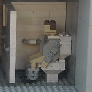 A Lego man using the toilet at Grand Central Station