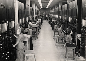 Two rows of control panels with dials and switches. Operators sit at them on four-legged stools