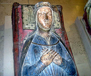 A photograph of a medieval tomb with a carving of Isabella on top. She is lying with her hands clasped, wearing a blue dress.