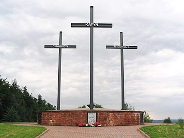 A memorial consisting of three crosses standing on a large brick pedestal. Each cross bears a name – Katyn, Kharkiv, or Mednoye.