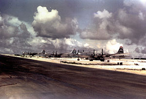 Color photo of three silver four engined World War II-era aircraft neatly lined up alongside a runway