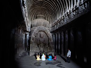 "people sitting before stone shrine the Buddhist ""Carpenter's Cave"" at Ellora in Maharashtra, India"