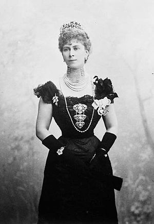 Thin Mary wearing a formal dress, a rope of pearls and a tiara
