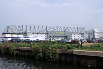 The exterior of Carrow Road, an association football stadium. A river is in the foreground.
