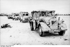 a black and white photograph of a column of vehicles covered in snow