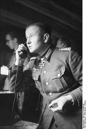 Black-and-white portrait of a man on the phone in semi profile wearing a military uniform with an Iron Cross displayed at his neck. He is holding a cigarette in his left hand.