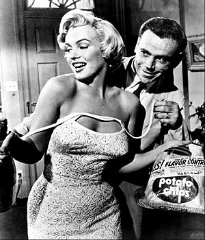 Monroe in The Seven Year Itch. She is holding a bag of chips and wearing a dress, which shoulder straps are undone. Behind her is Tom Ewell, who is holding the straps.