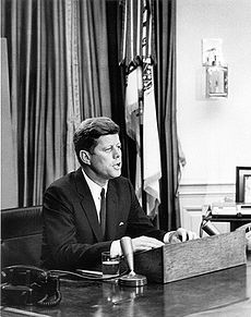 A black and white photograph of President John F. Kennedy speaking into a microphone at his desk in the Oval Office of the White House